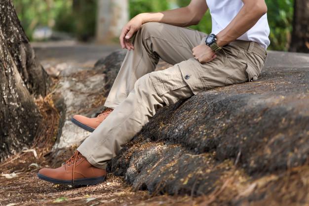 En mand sidder med beige cargo bukser i naturen